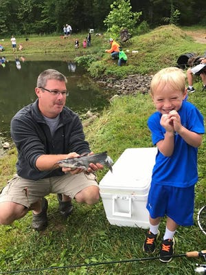 Young angler Baylor Harpe, son of Nic and Christi Harpe of Fairview, is not certain he wants to hold up his first catch of the day for a photo. Pictured - Baylor with his uncle Alan Brewer at the Fairview Youth Fishing Rodeo.