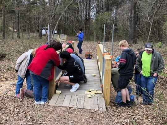 Volunteers work to repair the vandalized walking bridge on the Clysta Willett Nature Trail.