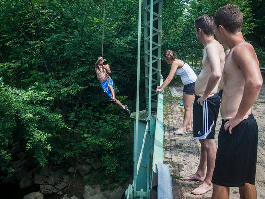 Kids in the summer of 2014 swing from ropes tied to