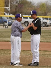 Kirtland Central coach Danny Secrest instructs pitcher Bryson Dowdy during a game against Aztec on Saturday at Kirtland Central High School.