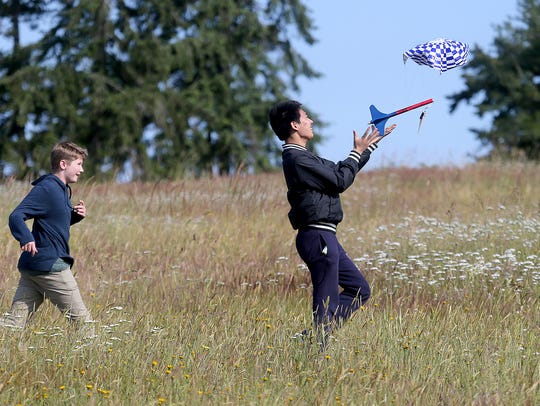 West Sound Academy ninth-grader Michael Gao catches his rocket after he launched it into the air on Wednesday. The STEM class built and launched the rockets. Behind him is student Henri Bothell, 13.
