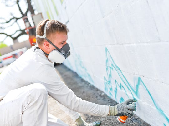 Artist Beau Thomas is painting a mural on a 110'-foot-long exterior wall at Kuehn Printing in Green Bay. The mural is one of several located in the Olde Main Street Arts District of downtown Green Bay.