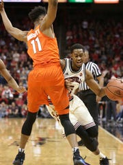 Louisville's V.J. King is bumped as he tries to advance