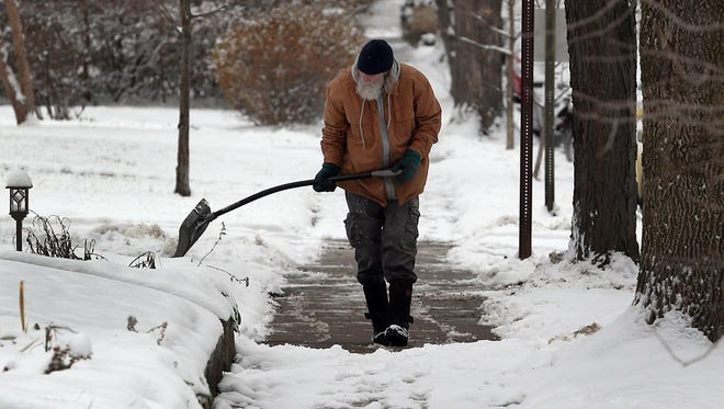 Woodruff Place residence work to clear the snow from their sidewalks following the overnight snowfall.