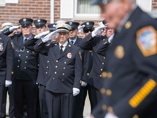 Firefighters salute during ceremonies on Sunday to