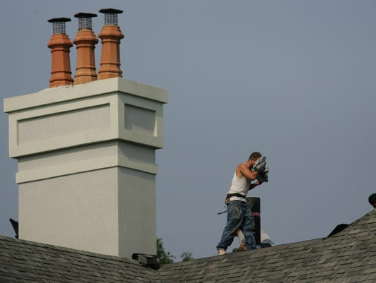 ROOFERS WORKING IN THE HEAT: Employees of Homestead Roofing do repairs on a roof at a home on Hunter Ridge Rd Thursday morning as the temperature rises in the high 90s.