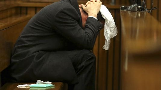 With a bucket at his feet, Oscar Pistorius listens to cross-questioning about the shooting death of his girlfriend Reeva Steenkamp in Pretoria, South Africa, on Monday.