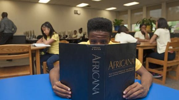 Moses Scott-Ali, age 13, reads a book along with other students at the Lawnside Public School library.