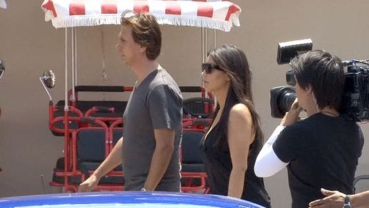 Kim Kardashian and her friend and publicist Jonathan Cheban walk the Seaside Heights boardwalk.