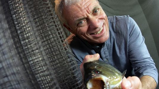 Host Jeremy Wade pets a black piranha, one of the animals featured on his show 'River Monsters.'