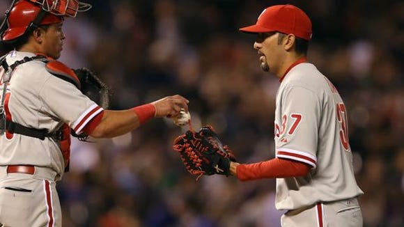 Phillies catcher Carlos Ruiz gives the ball to relief pitcher Mike Adams as he enters the game to face the Colorado Rockies in the sixth inning at Coors Field on April 18.