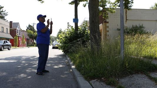 A Bond Hill resident takes pictures of a lot with overgrown grass on California Avenue.