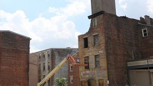 A building being torn down near Findlay Market in Over-the-Rhine on Monday. City Council has voted to give 3CDC the right to develop more than 30 properties north of Liberty Street.