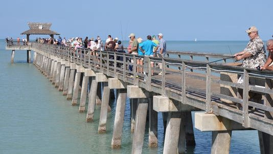 Crowds walk along the Naple Pier.