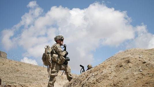 A U.S. soldier patrols on the edge of a village in Afghanistan, in March.