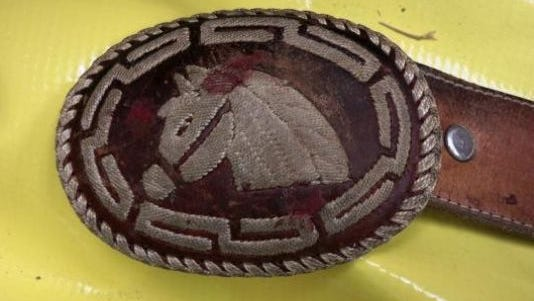 This undated photo released by the Park County Sheriff's Office in Cody, Wyo., shows a belt buckle found on a decapitated man who was riddled with bullets and found in remote Northwestern Wyoming.