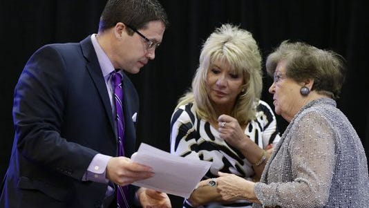 Brian Ohorilko, administrator with the Iowa Racing and Gaming Commission, left, and commissioners Dolores Mertz, right, and Kris Kramer, center, go over papers before the Iowa Racing and Gaming Commission rejected a proposed $164 million casino in Cedar Rapids.