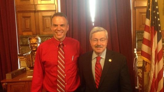 Nick Rhoades, left, stands with Iowa Gov. Terry Branstad at the bill signing for the updated infectious disease transmission law.