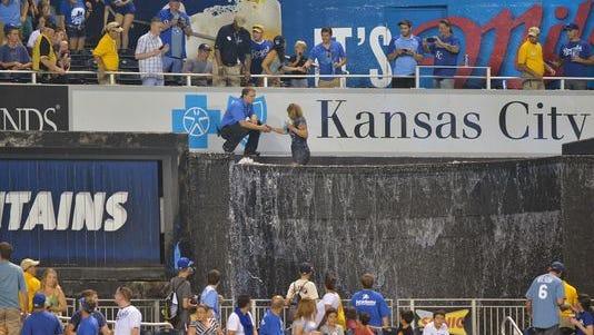 Kansas City Royals security helps Jessica McCoy out of the Kauffman Stadium fountains during the seventh inning of a game between the Royals and the Minnesota Twins on Aug. 5, 2013.