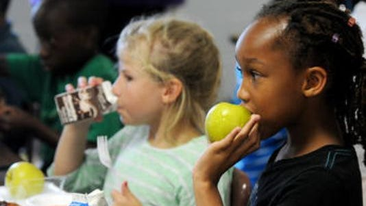 Children from around Hattiesburg eat free lunch at N.R. Burger Middle School during the 2014 Summer Food Service kickoff.