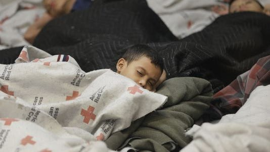 FILE - This June 18, 2014, file photo shows children detainees sleeping in a holding cell at a U.S. Customs and Border Protection processing facility in Brownsville,Texas. Thousands of immigrant children crossing alone into the U.S. can live in American cities, attend public schools and possibly work here for years without consequences. The chief reasons are an overburdened, deeply flawed system of immigration courts and a 2002 law intended to protect children's welfare, an Associated Press investigation finds. (AP Photo/Eric Gay, Pool)