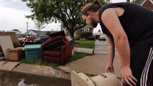Randy Quick of Center Line empties water from a heater while helping his parents carry items to the trash from their house on McKinley that were in a flood on Tuesday, Aug. 12, 2014, after heavy rains flooded many areas in metro Detroit.