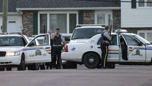 Royal Canadian Mounted Police officers take cover behind their vehicles in Moncton, New Brunswick, on Wednesday.