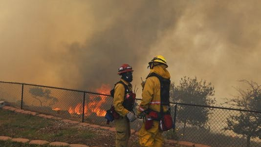 Two firefighters discuss a strategy change while fighting a wildfire from the backyard of a home on May 15, 2014, in San Marcos, Calif.