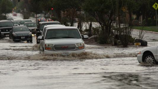 Motorists in Cathedral City, near Palm Springs, Calif., as deep water collects in the roadway while a storm rolls through.