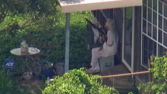 An elderly woman is seen sitting outside her Channelview, Texas, home July 31, 2014, holding a shotgun before deputies took her into custody.