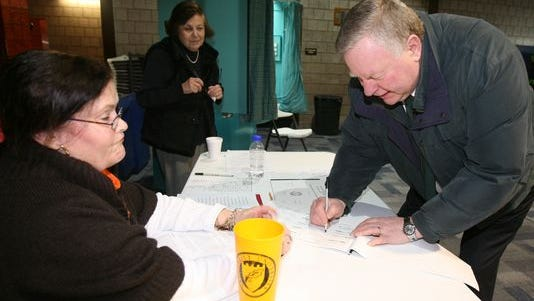 Acting Village Judge Michael O'Toole, signs the election register as he prepares to vote in the Village of Tuckahoe elections at the Tuckahoe Community Center, March 18, 2014. Looking on are election inspectors Virginia Marciano and Adelaide DiGiorgi. (Photo: Mark Vergari/The Journal News)