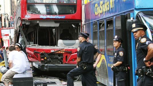 People and police officers stand at the scene of an accident between two double-decker buses at Duffy Square in Times Square on August 5, 2014 in New York City. At least 13 people were injured when the buses collided at 47th Street and Seventh Avenue.(Photo: Monika Graff/Getty Images)
