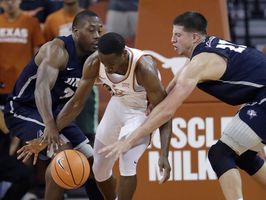 Texas guard Matt Coleman (2) is pressured by New Hampshire defenders Jacoby Armstrong, left, and Tanner Leissner during the first half of an NCAA college basketball game, Tuesday, Nov. 14, 2017, in Austin, Texas. (AP Photo/Eric Gay)