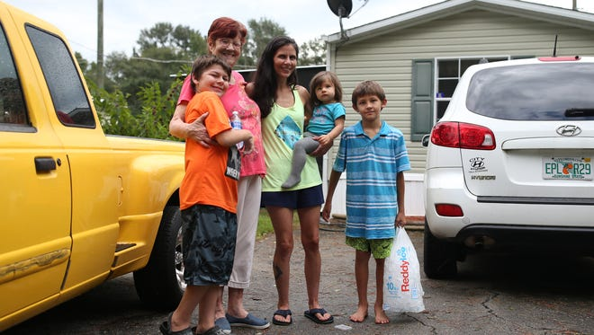 """Mary Jo Foskey (center left) and her neighbors (left to right) Lee, 12, Melissa, Essie, 18 mo., and Parker Wilkerson, 8, pose in her front yard at Greenwood Trailer Park while they wait for power to be restored Wednesday. As Parker put it, """"The thing this trailer park goes by is everyone in this trailer park is a family. And we all work together."""""""