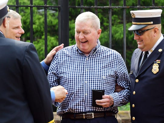 Retired firefighter Tim Bair is greeted by, from left, York City Fire Chief Dave Michaels, York City Mayor Michael Helfrich and York City Deputy Fire Chief Chad Deardorff during a recognition of retired firefighters at the York City Fire Department's awards ceremony at York City Hall on Thursday, Aug. 16, 2018. Bill Kalina photo