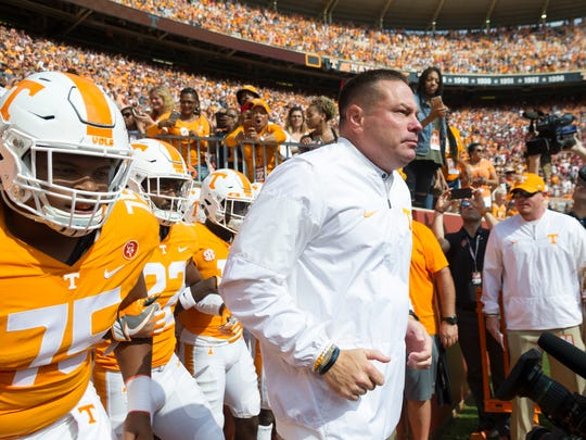 Tennessee Head Coach Butch Jones runs out of the locker room with the team during the Tennessee Volunteers vs South Carolina Gamecocks game at Neyland Stadium in Knoxville, Tennessee on Saturday, October 14, 2017.