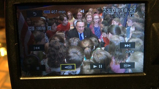 Surrounded by third-graders at Brewer Community School in Brewer, Maine, Maine Gov. Paul LePage signs a bill April 4, 2016, making lobsters the official state crustacean.
