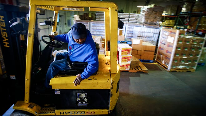 Mid-South Food Bank forklift operator Fred Jones grabs palettes of donated foods that will be given to a area charitable organization to help feed the needy.