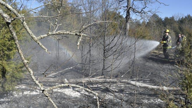 Mountain Home firefighters extinguish the smoldering remains of a brush fire at 1766 West Road on Sunday afternoon.