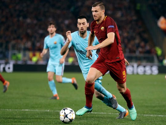 Roma's Edin Dzeko is challenged by Barcelona's Sergio Busquets during the Champions League quarterfinal second leg soccer match between Roma and FC Barcelona at Rome's Olympic Stadium, Tuesday, April 10, 2018. (AP Photo/Andrew Medichini)