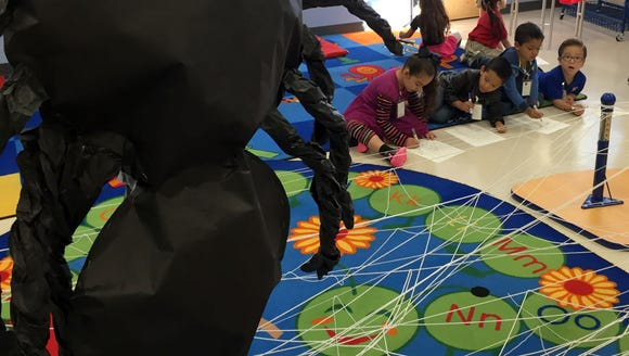 Students draw a spider in an Ysleta Pre-K Center class