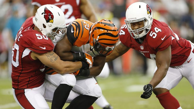 Cincinnati Bengals running back Giovani Bernard (25) is dragged down by the Arizona Cardinals inside linebacker Larry Foote (50) and inside linebacker Kenny Demens (54) in the first quarter at the University of Phoenix Stadium.