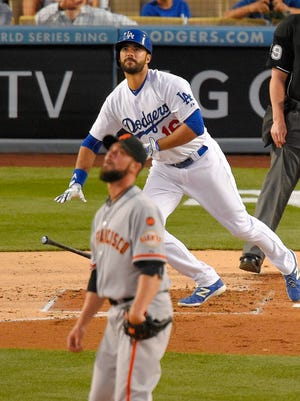 Andre Ethier, right, starts towards first as Giants starting pitcher Ryan Vogelsong watches the ball leave the park.