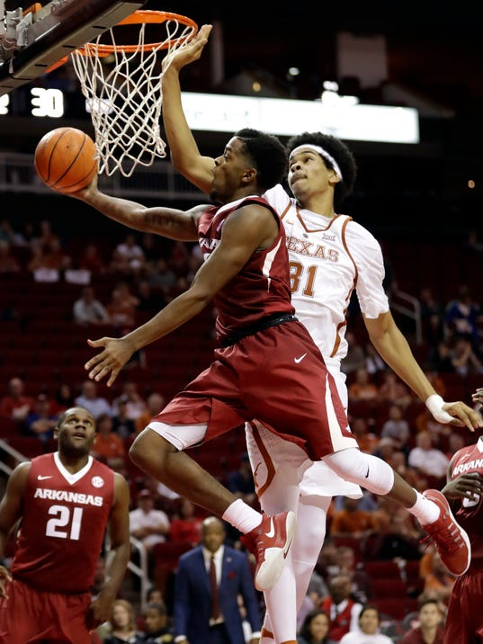 FILE - In this Dec. 17, 2016, file photo, Arkansas' Daryl Macon (4) goes up to shoot as Texas' Jarrett Allen (31) defends during the second half of an NCAA college basketball game, in Houston. Macon wanted to quit basketball, and school, when he found out junior college was his only path to the Razorbacks. Luckily for Arkansas, the senior didn't and has instead transformed the program with his outgoing personality _ along with his play. (AP Photo/David J. Phillip, File)