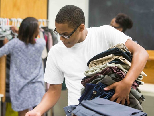 A.I. duPont junior Brendan Jones, 17, helps organize stacks of donated clothes from school faculty members.