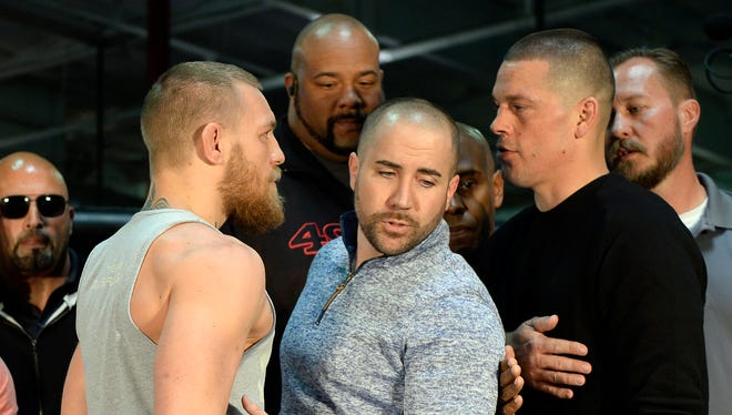 UFC featherweight champion Conor McGregor (L) and lightweight contender Nate Diaz (R) are held apart by Dave Sholler (C), UFC vice president of public relations, after a news conference at UFC Gym in Torrance, Calif.
