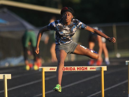 Gadsden County's Janasia Cox clears a hurdle during