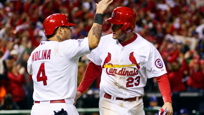 Cardinals third baseman David Freese and catcher Yadier Molina celebrate after scoring runs against the Dodgers during Game 6 of the NLCS at Busch Stadium.