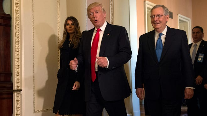 In this Nov. 10, 2016, photo, President-elect Donald Trump, accompanied by his wife Melania, and Senate Majority Leader Mitch McConnell of Ky., gestures while walking on Capitol Hill in Washington. Washington's new power trio consists of a bombastic billionaire, a telegenic policy wonk, and a taciturn political tactician. How well they can get along will help determine what gets done over the next four years, and whether the new president's agenda founders or succeeds.