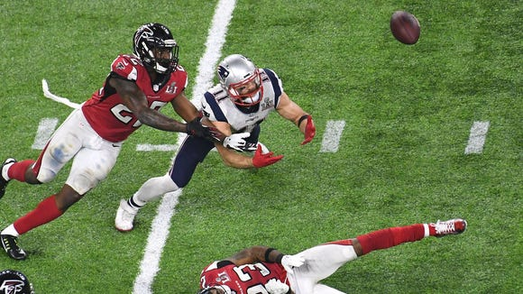 New England Patriots wide receiver Julian Edelman (11) and Atlanta Falcons strong safety Keanu Neal (22) dive to catch a tipped pass in the fourth quarter during Super Bowl LI at NRG Stadium.
